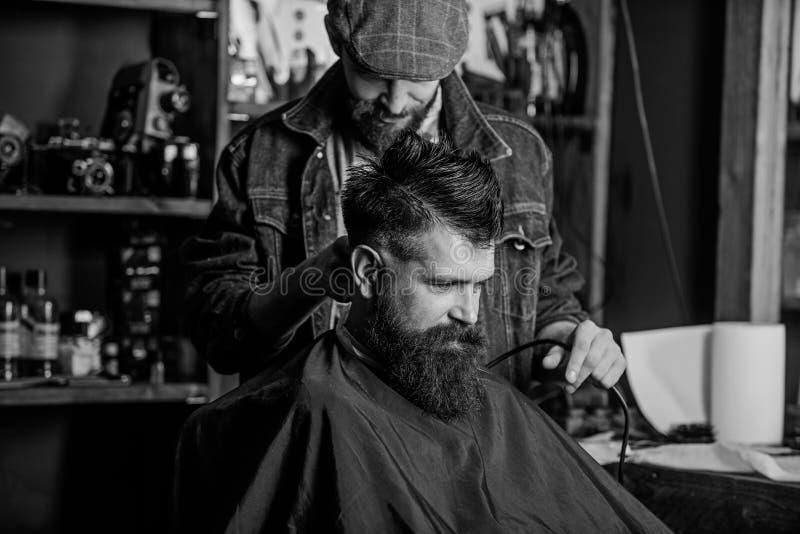 有头发剪刀工作的理发师在有胡子的人理发店背景理发  行家发型概念 理发师与 库存图片