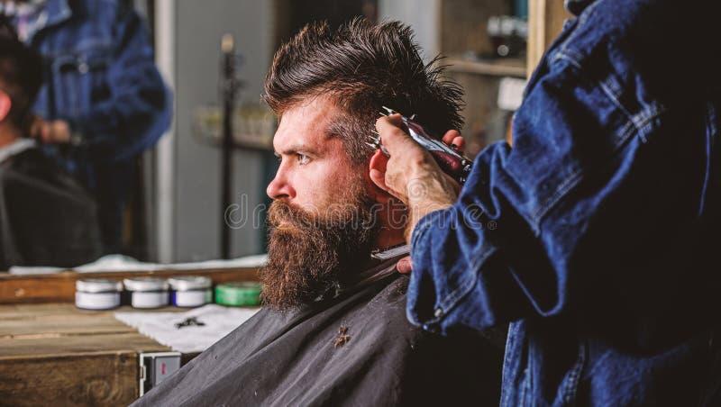 有头发剪刀工作的理发师在有胡子的人理发店背景的发型 r barby 免版税库存照片