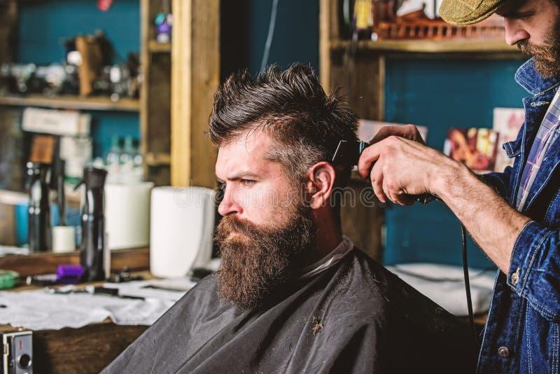 有头发剪刀的理发师在人的发型工作有胡子的,理发店背景 称呼头发有胡子的理发师 免版税库存图片