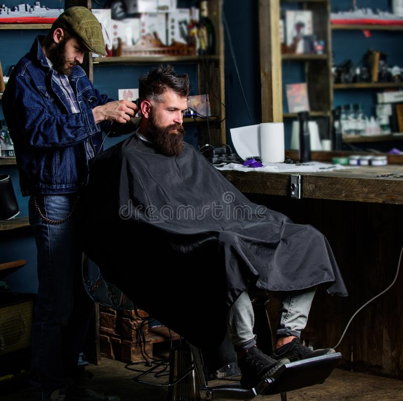 有头发剪刀的理发师在有胡子的人理发店背景理发工作 得到理发的行家客户 barby 免版税库存图片