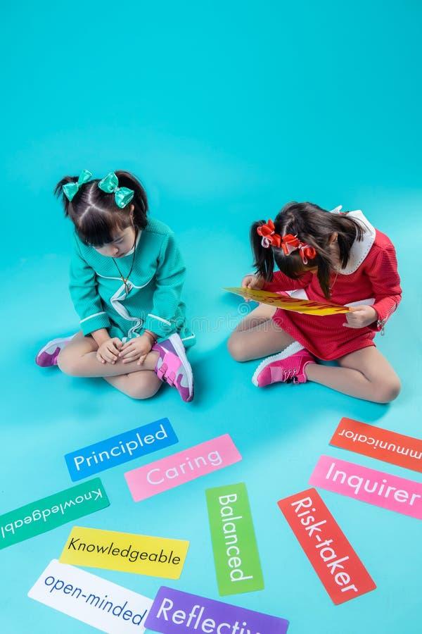 有头发尾巴的女孩殷勤地读词的在五颜六色的标识牌 免版税库存图片