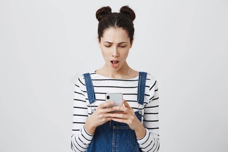 有头发结的震惊深色的少妇在整体的牛仔布,在智能手机的收到的消息有坏消息的,是 免版税库存图片