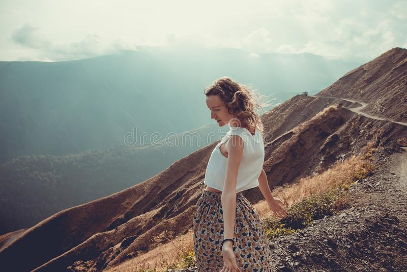 有头发风的浪漫自由的少妇享受与自然和新鲜空气的和谐 给蒲公英领域开花的长发头脑和平松弛白人妇女年轻人穿衣 愉快的平静的女孩,启发 免版税库存图片