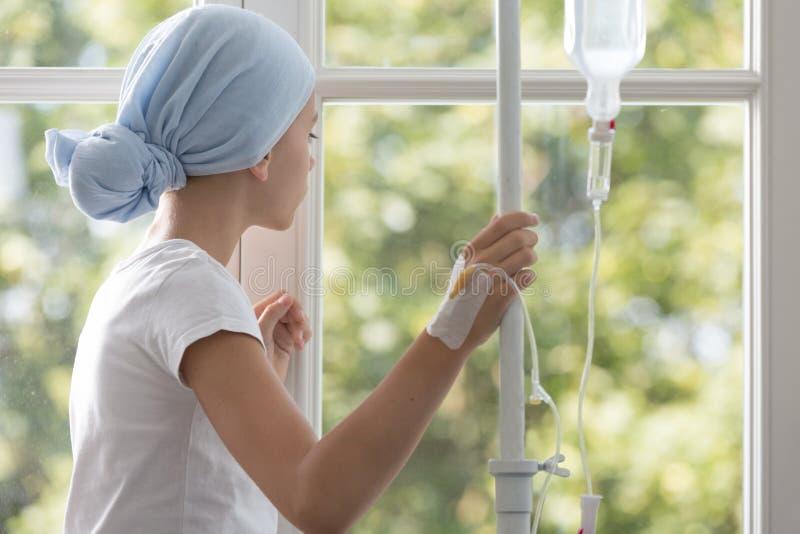 有头戴蓝色头巾的滴水的病的孩子在医院 免版税库存图片
