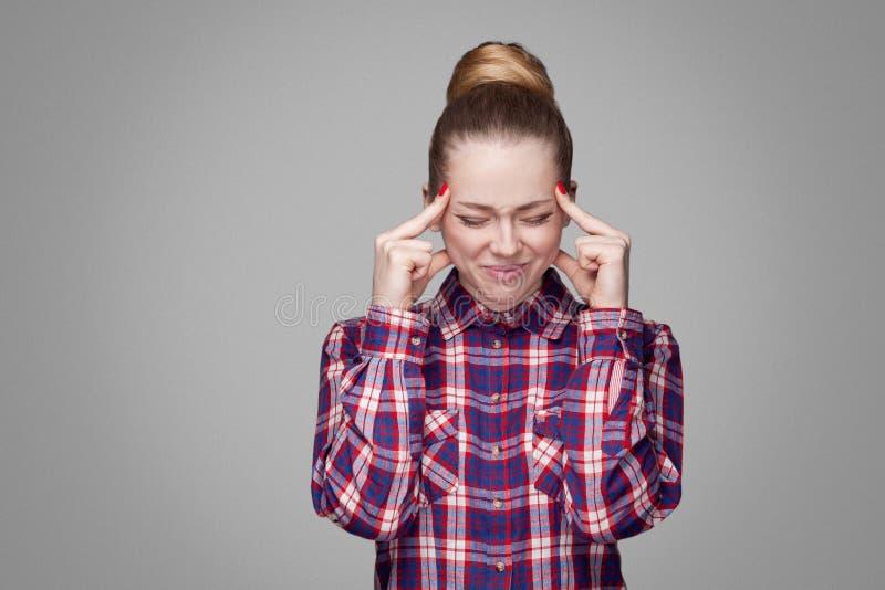 有头疼的不快乐的白肤金发的女孩在红色,桃红色方格的衬衣,收集的小圆面包发型,接触她的头与的构成身分 库存照片