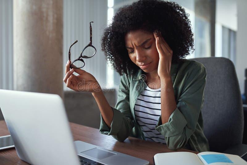 有头疼的劳累过度的非洲女商人在办公室 免版税库存照片