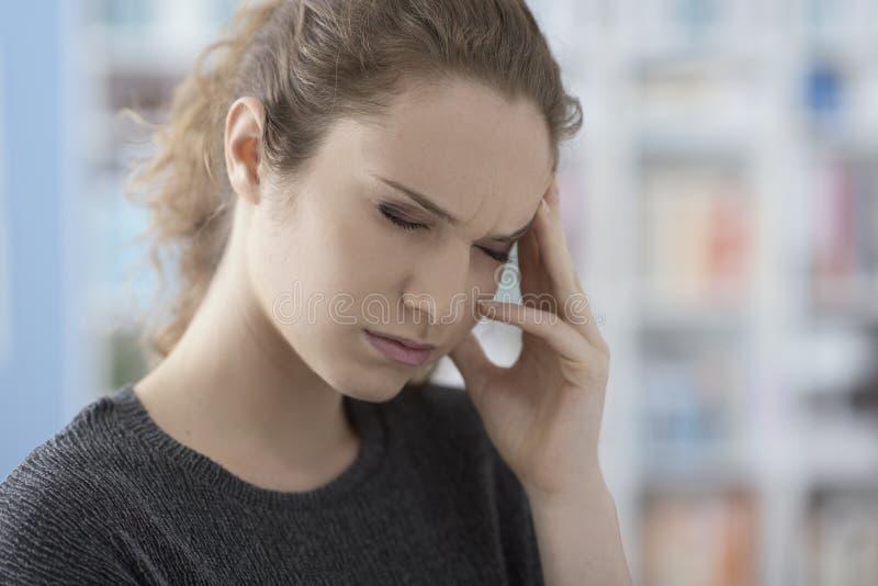 有头疼的年轻女人 免版税库存图片