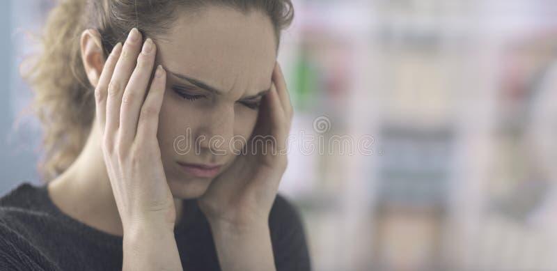 有头疼的年轻女人 免版税库存照片