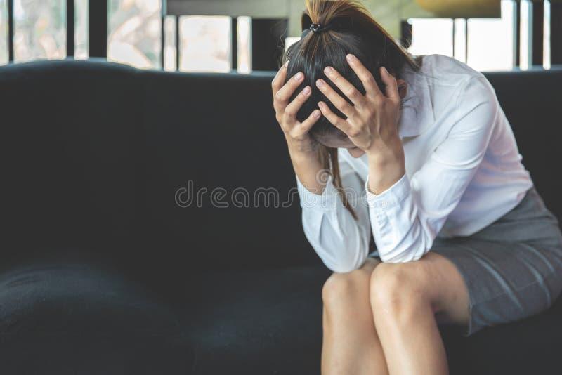 有头疼的被注重的妇女在沙发 哀伤的妇女 疏忽工作 免版税库存照片