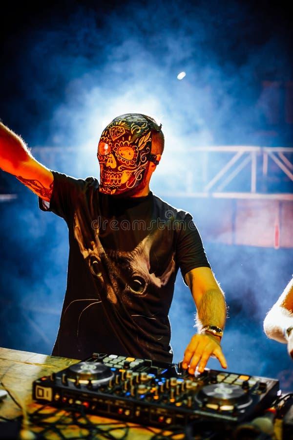 有头骨的DJ掩没演奏电子音乐在夏天党费斯特 免版税库存照片
