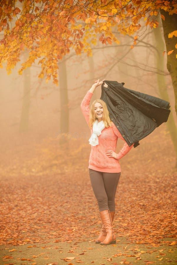 有夹克的微笑的时尚妇女在公园 免版税库存图片