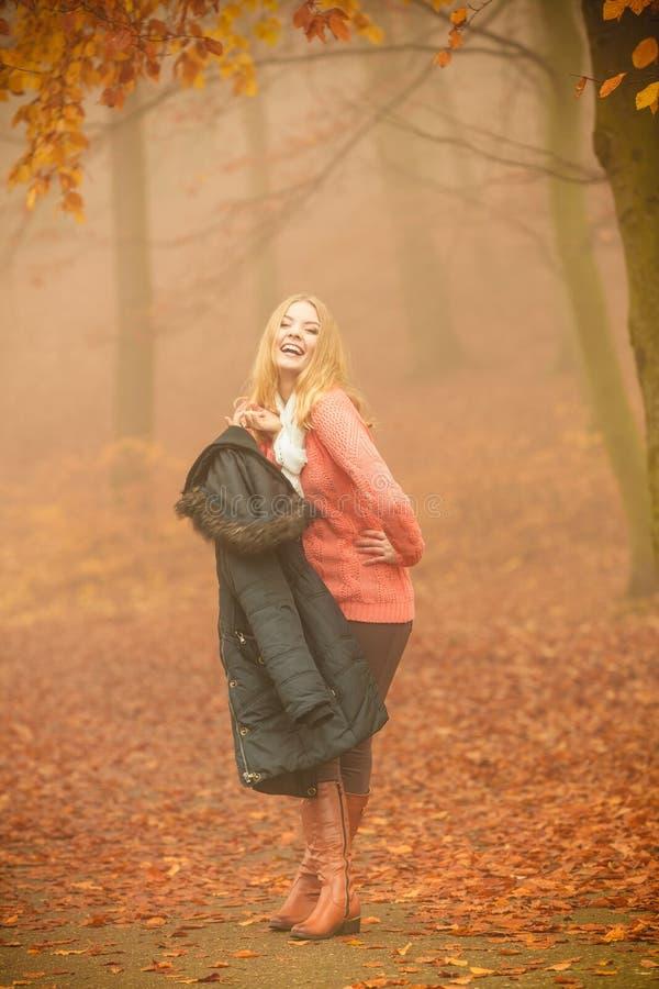 有夹克的微笑的时尚白肤金发的妇女在公园 库存图片