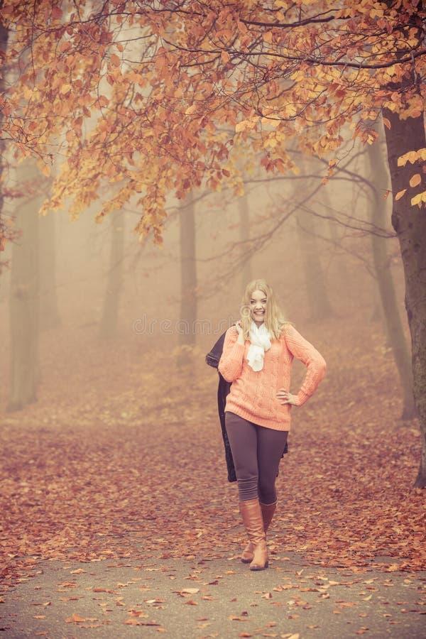 有夹克的微笑的时尚白肤金发的妇女在公园 库存照片