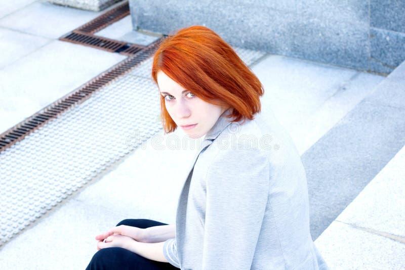 有夹克的红头发人美丽的妇女坐台阶 库存照片