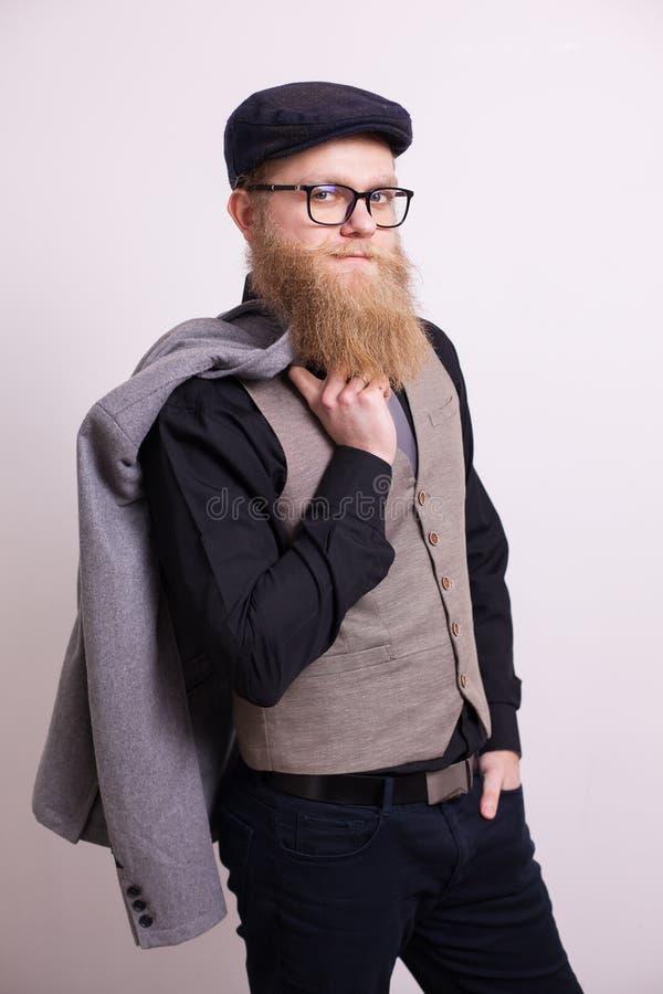 有夹克的英俊的有胡子的人在他的看确信在白色背景的照相机的肩膀 免版税图库摄影
