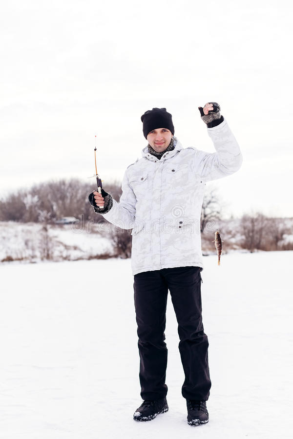 有夹具的冬天在冻湖的渔夫和鱼 库存图片
