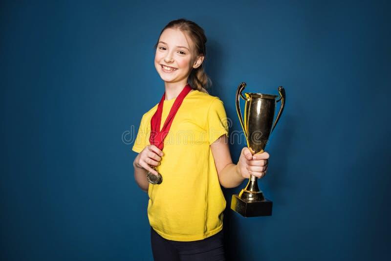 有奖牌和战利品杯子的激动的女孩 免版税图库摄影