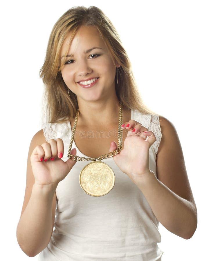 有奖牌的年轻十几岁的女孩微笑在白色的 图库摄影