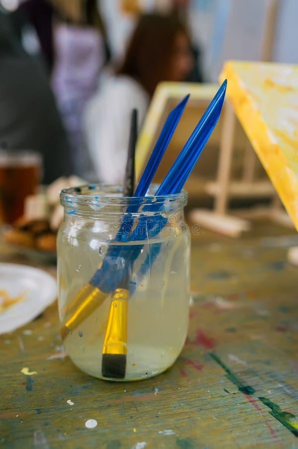 有套的玻璃瓶子在木桌上的刷子 艺术家画笔 库存图片