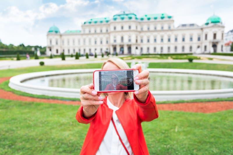 有奥地利的旗子的女性旅客反对上部贝尔维德雷宫的背景的在维也纳 免版税库存图片