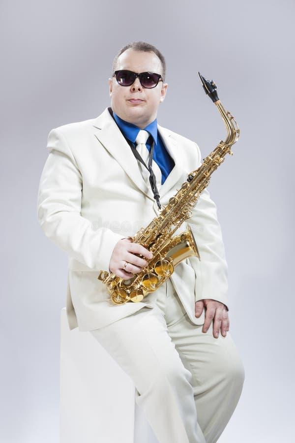 有女低音萨克斯管的英俊的白种人音乐家 免版税库存照片