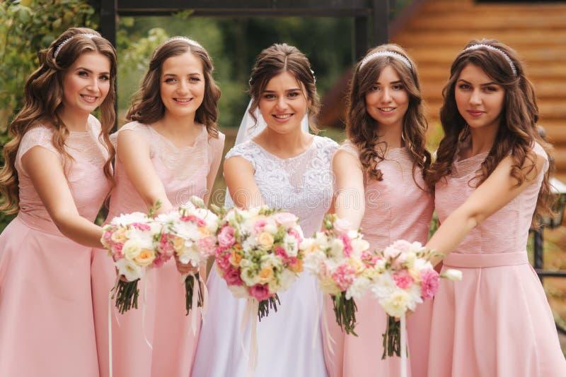 有女傧相外面举行花束的愉快的新娘和获得乐趣 同样礼服的美丽的女傧相支持 免版税库存照片