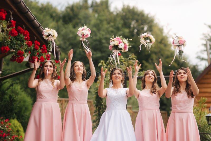有女傧相外面举行花束的愉快的新娘和获得乐趣 同样礼服的美丽的女傧相支持 免版税库存图片