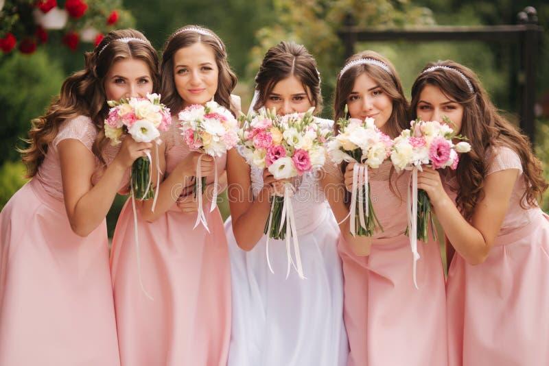 有女傧相外面举行花束的愉快的新娘和获得乐趣 同样礼服的美丽的女傧相支持 免版税图库摄影