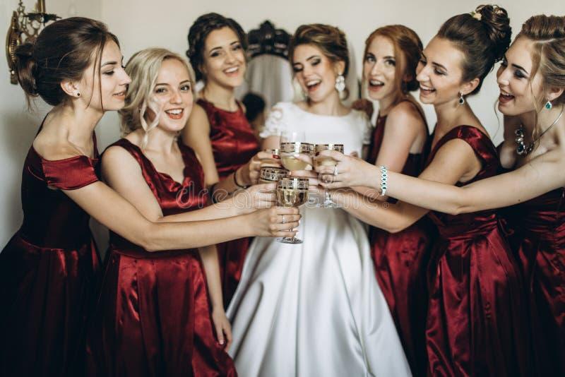 有女傧相的愉快的时髦的华美的白肤金发的新娘后面的 免版税库存照片