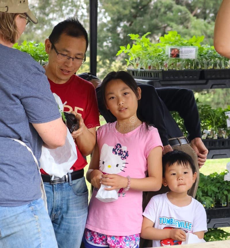 有女儿和儿子购买植物的亚裔遗产父亲庭院的显示土尔沙俄克拉何马美国4 13 2018年 免版税库存照片