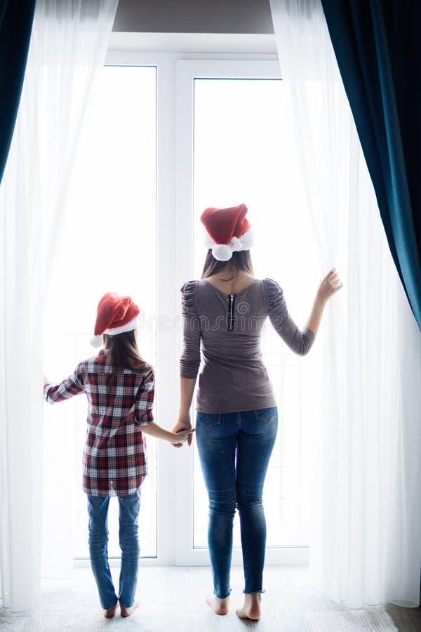 有女儿开窗口的年轻母亲在圣诞老人帽子的圣诞节早晨打开帷幕在舒适卧室早晨 库存照片