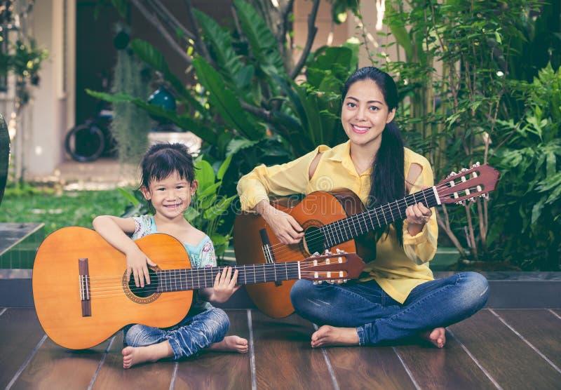 有女儿戏剧吉他的母亲 一起花费时间的系列 库存图片