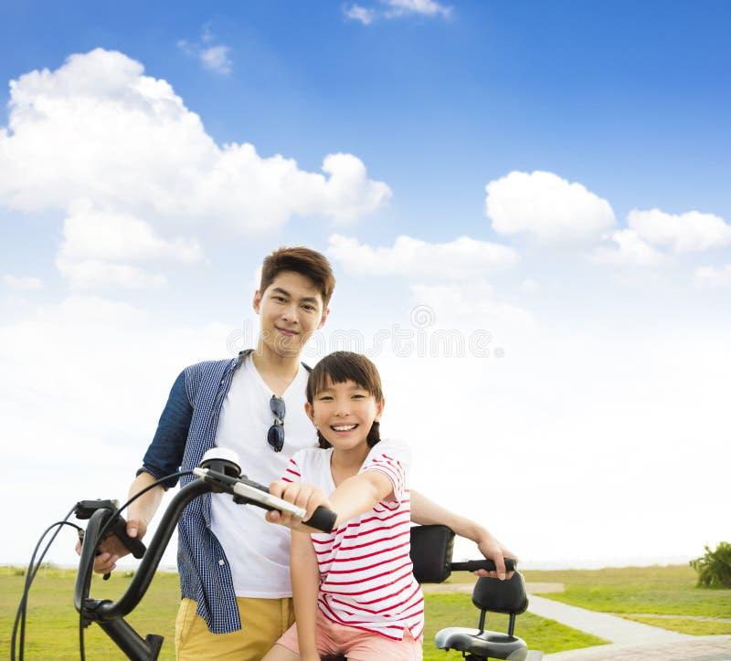 有女儿户外骑马自行车的父亲 免版税图库摄影