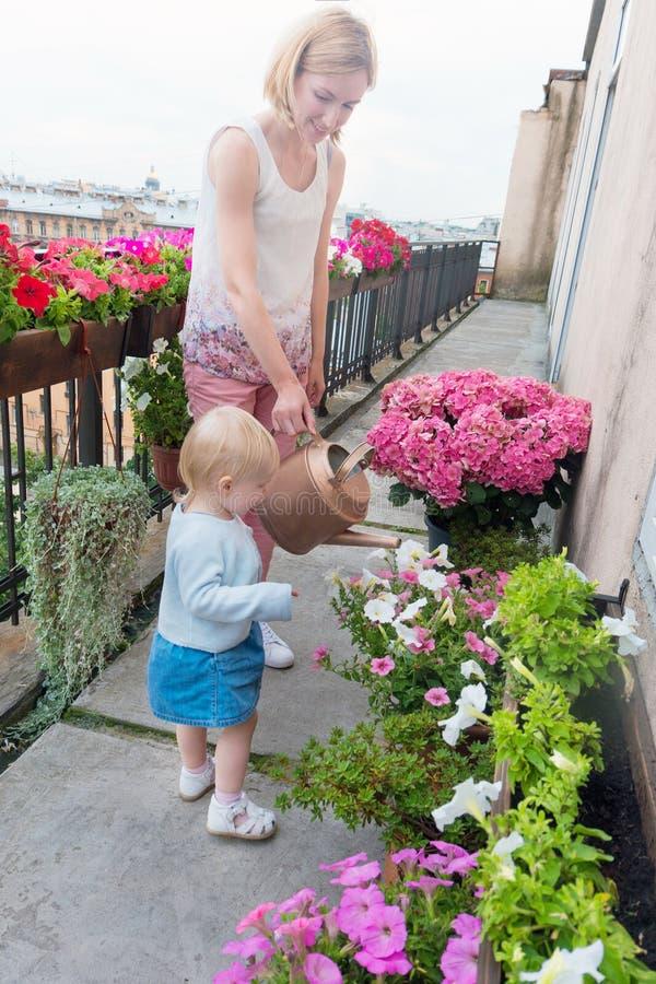 有女儿浇灌的花的母亲在阳台 图库摄影