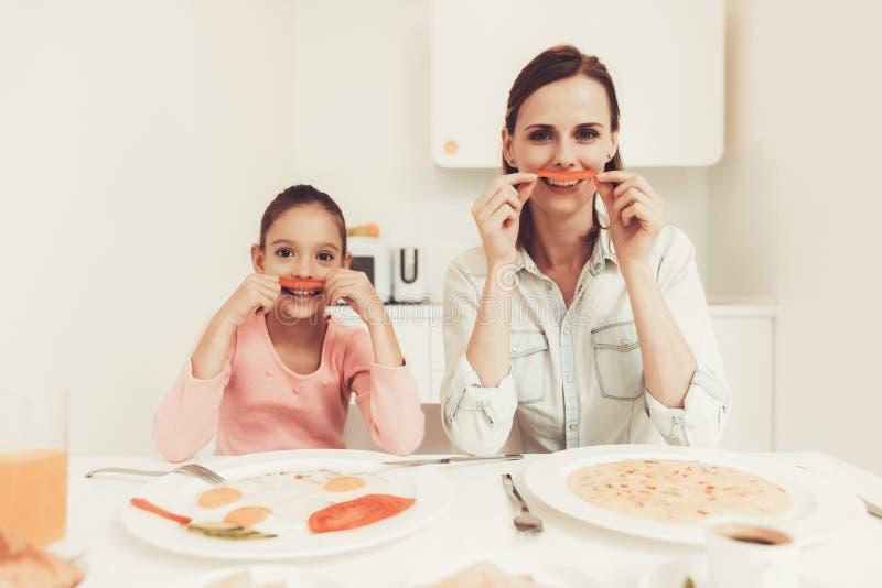 有女儿的妈妈吃晚餐在厨房 库存照片