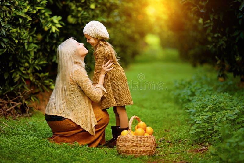 有女儿的愉快的妇女在晴朗的庭院里 免版税库存图片