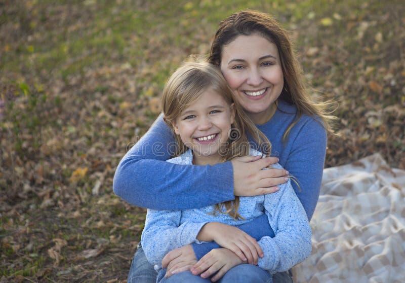 有女儿的愉快的年轻母亲在秋天公园 库存图片