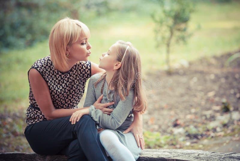 有女儿的新母亲在公园 库存照片
