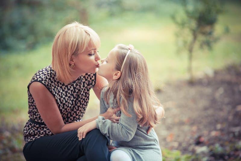 有女儿的新母亲在公园 免版税图库摄影