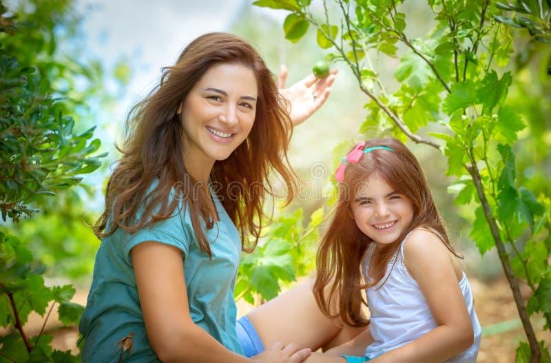 有女儿的母亲在果树园 免版税库存图片