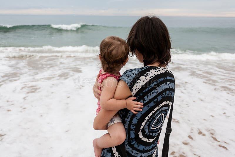 有女儿的母亲在海洋 免版税库存照片