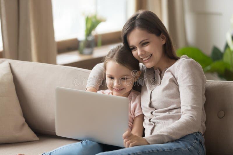 有女儿的母亲坐在膝上型计算机的长沙发电影 免版税库存图片