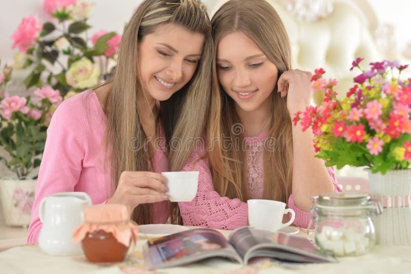 有女儿的母亲有杂志的 免版税库存图片