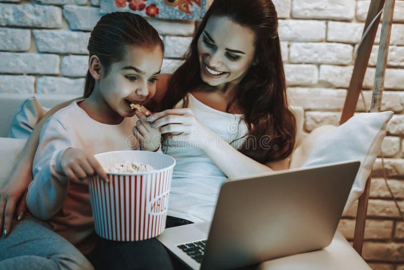 有女儿的母亲观看在膝上型计算机的录影 库存图片