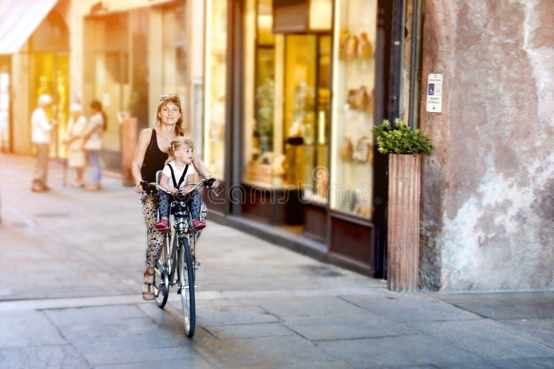 有女儿骑马自行车的妈妈在意大利 坐在安全位子的孩子 老狭窄的意大利镇 体育健康家庭 免版税图库摄影