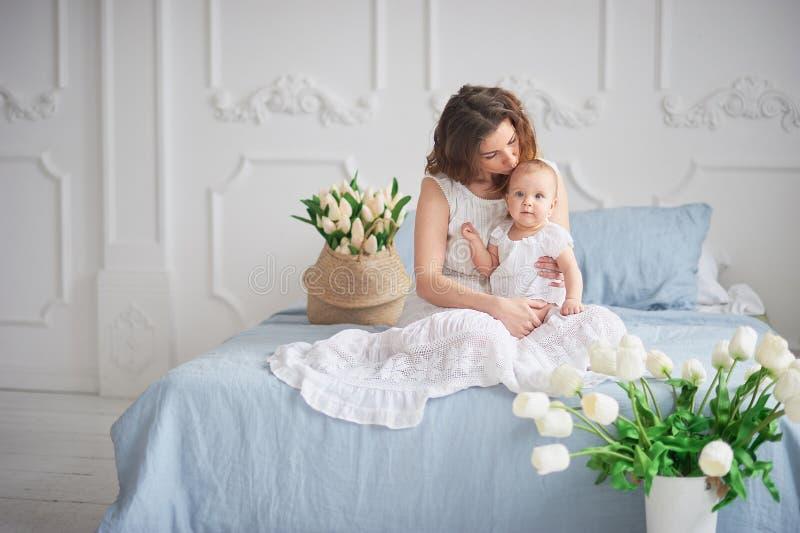 有女婴的美丽的年轻母亲她的胳膊的 一个愉快的家庭的概念,母性 使用与她的婴孩的母亲 免版税库存照片