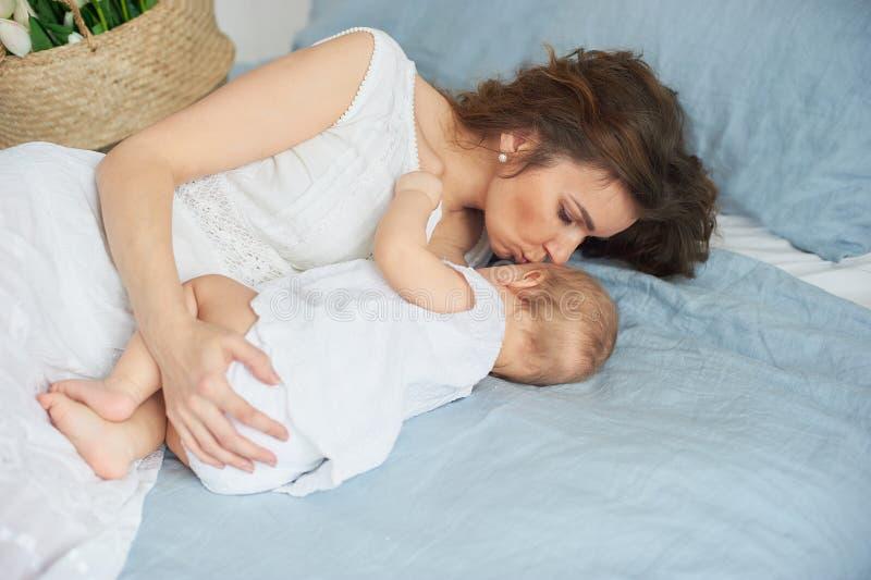 有女婴的美丽的年轻母亲她的胳膊的 一个愉快的家庭的概念,母性 使用与她的婴孩的母亲 库存图片