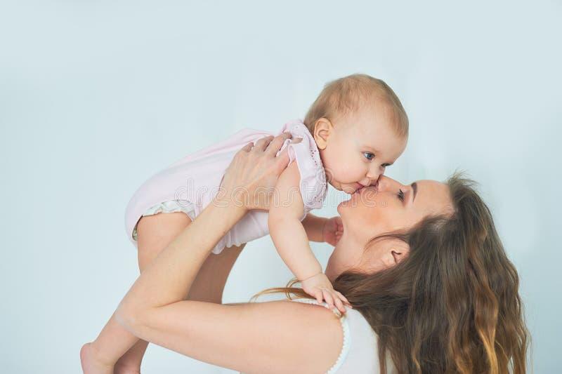 有女婴的美丽的年轻母亲她的胳膊的 一个愉快的家庭的概念,母性 使用与她的婴孩的母亲 免版税图库摄影