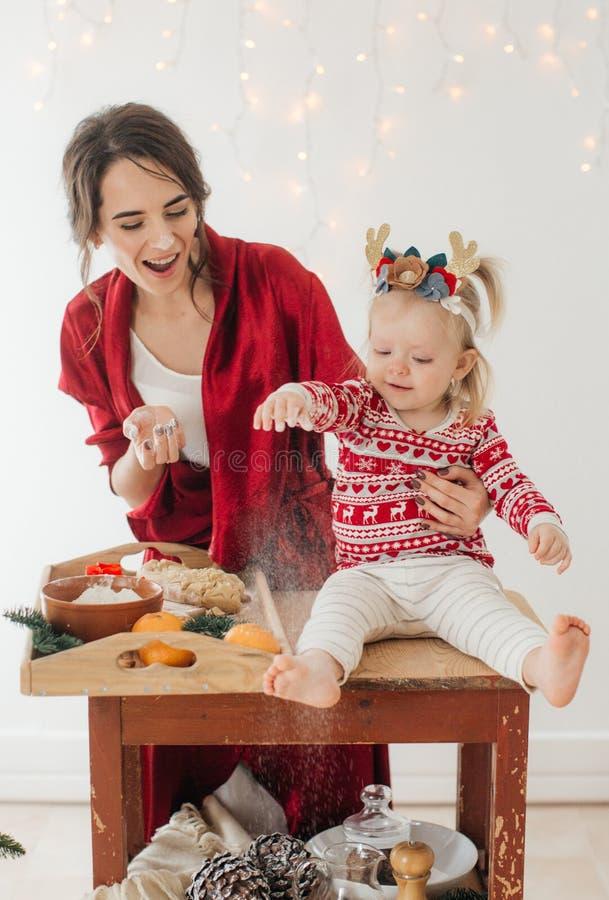有女婴的美丽的愉快的妇女在与礼物的一棵圣诞树附近 免版税库存图片
