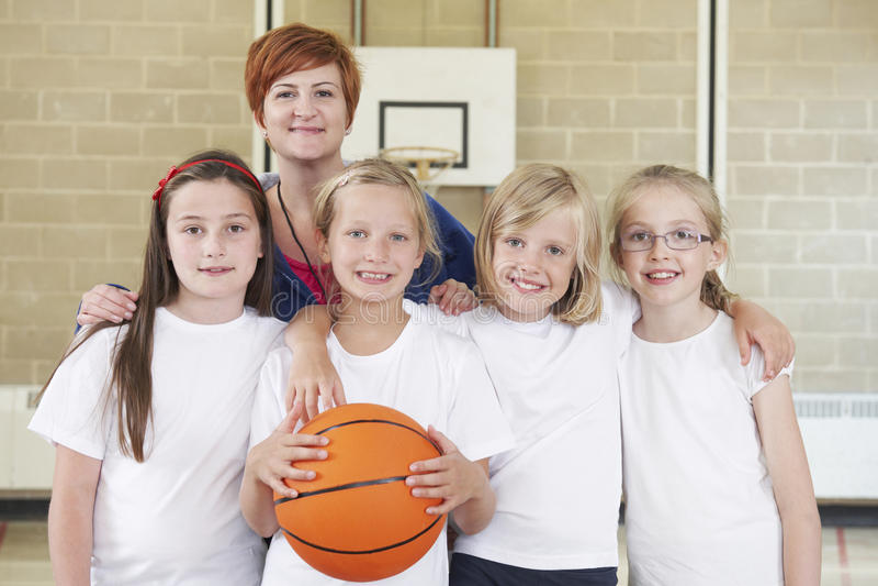 有女孩学校蓝球队的老师 免版税库存照片